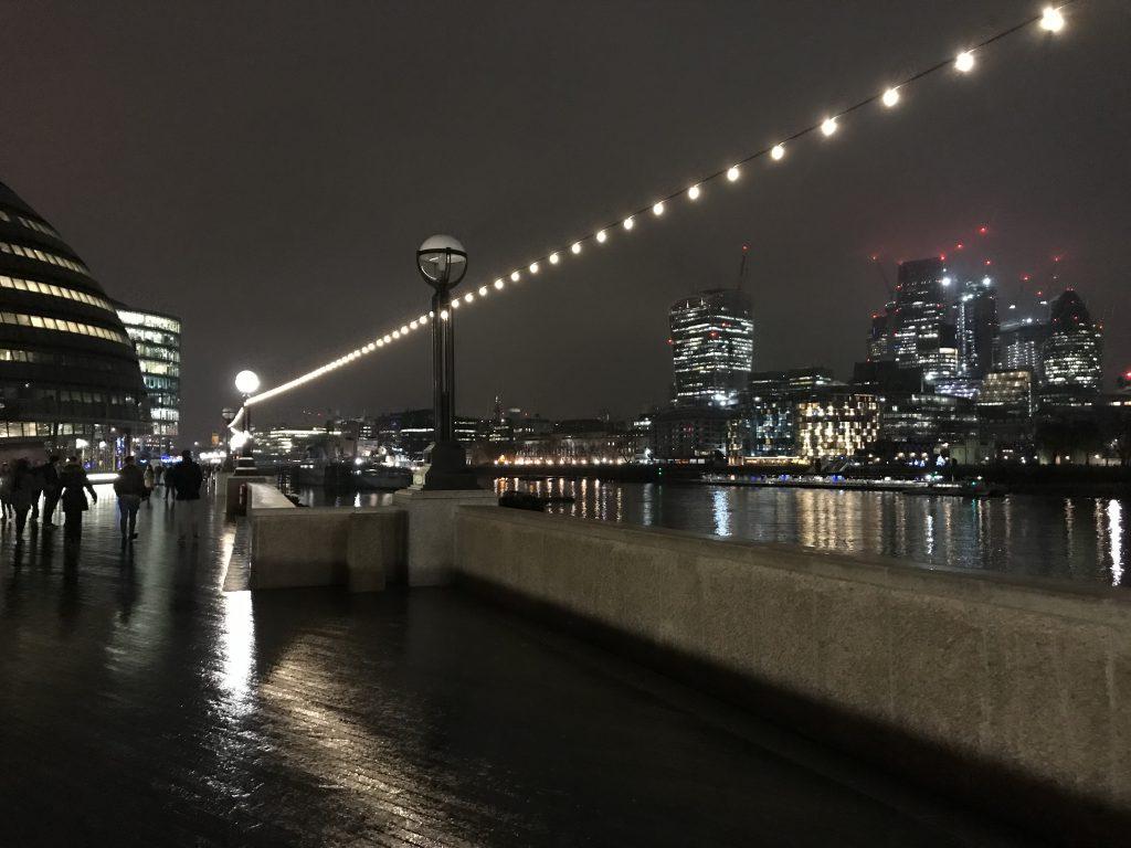Blick von der Uferpromenade der Themse auf London während eines Rundgangs bei Nacht